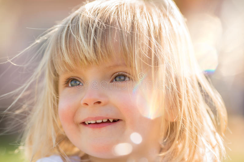 Happy smiling young baby caucasian blonde real people girl close outdoor portrait stock image
