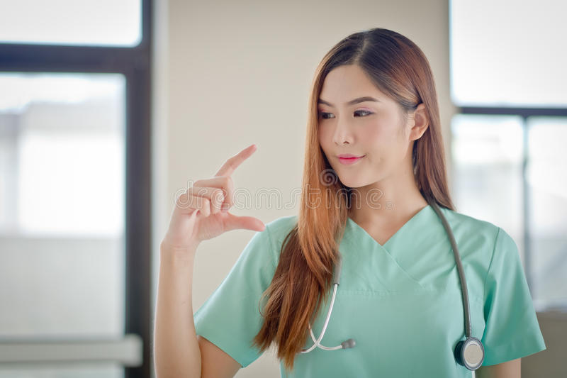 Happy smiling young beautiful female doctor showing blank area f royalty free stock images