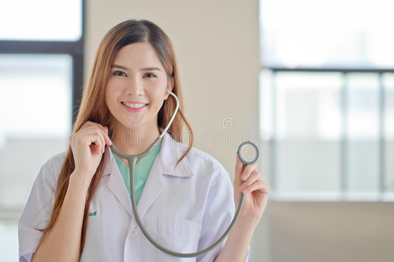 Happy smiling young beautiful female doctor showing blank area f stock photo