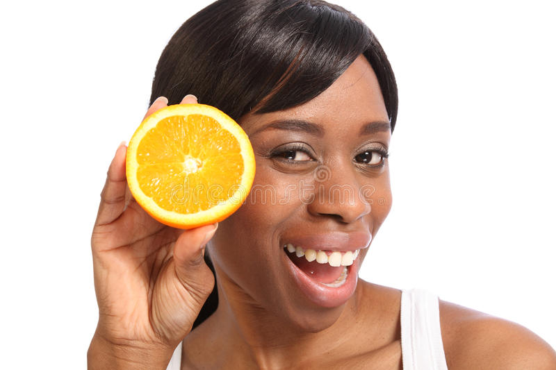 Happy smiling young black woman with orange fruit. Big happy smile and excited fun pose with orange slice by beautiful young black woman stock photos