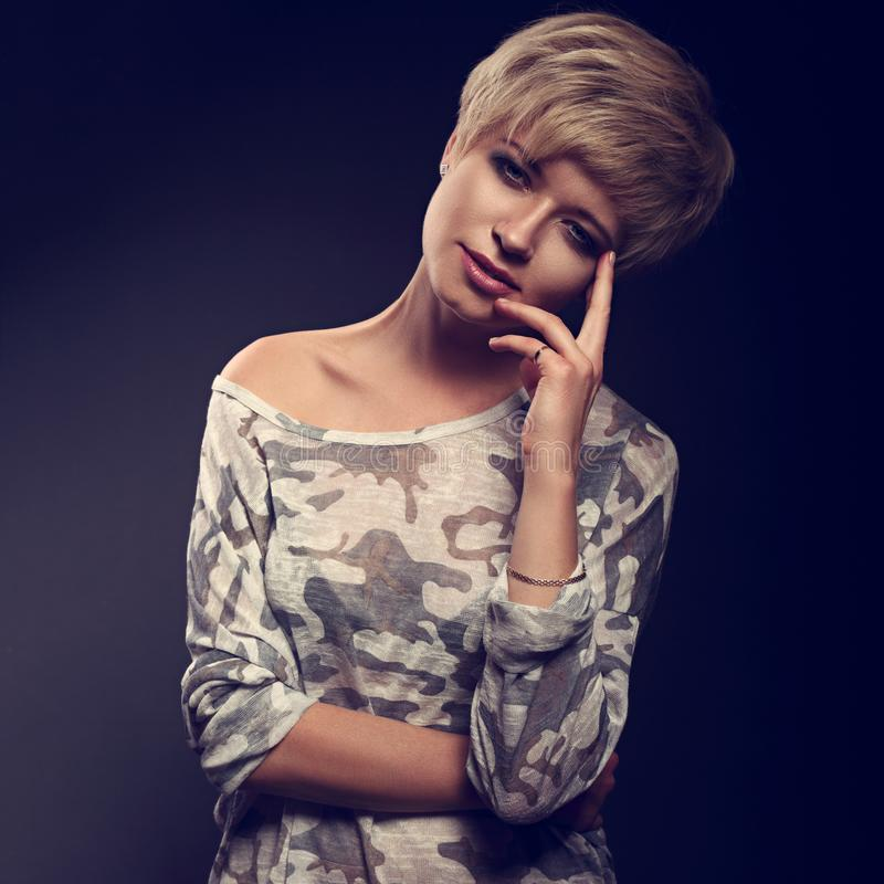 Happy smiling young blond woman with short bob hair style lookin. G in grey trendy tunic on dark background. Closeup toned portrait stock photography