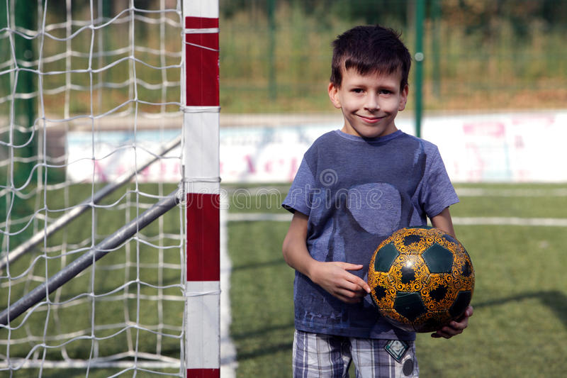 Happy smiling young boy with football ball stock photos