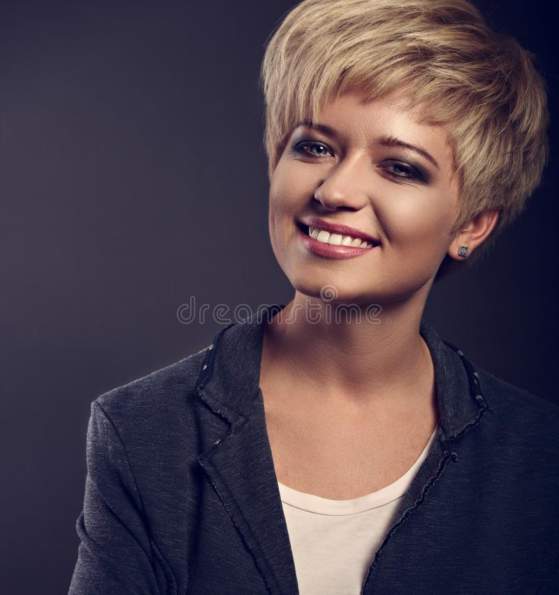Happy smiling young business blond woman with short bob hair sty. Le looking in grey trendy jacket on dark background. Toned closeup color portrait stock images