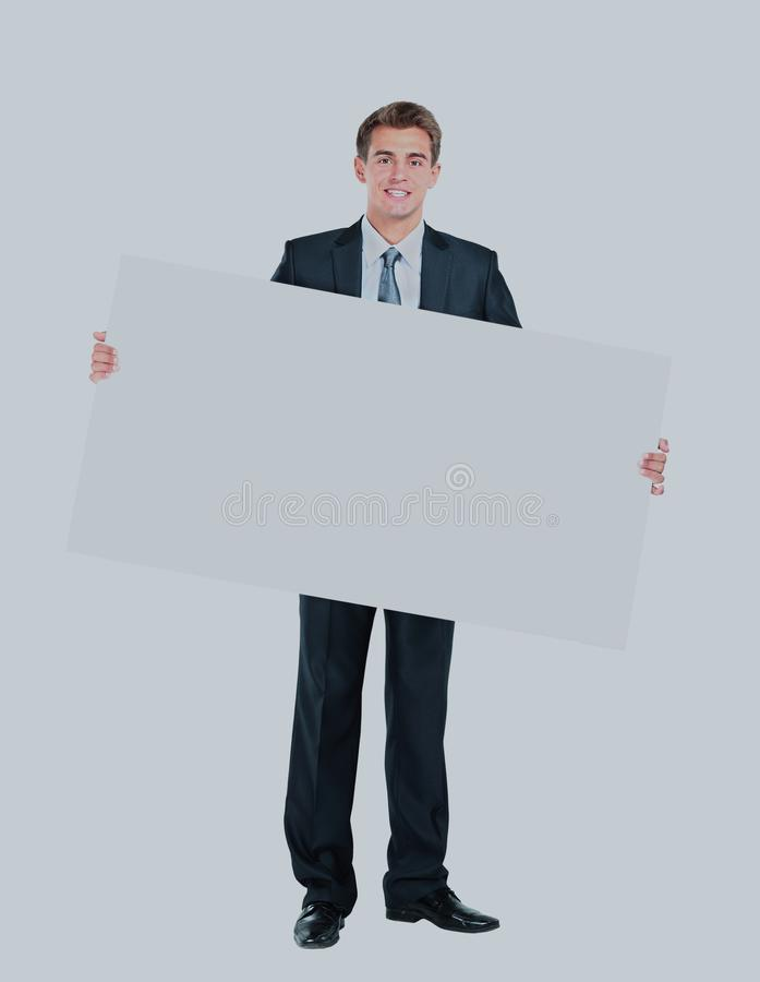 Happy smiling young business man showing blank signboard. Happy smiling young business man showing blank signboard stock image
