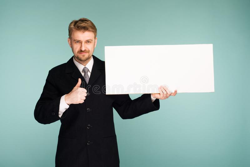 Happy smiling young business man showing blank signboard thumbs up royalty free stock images