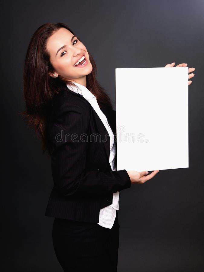 Happy smiling young business woman showing blank signboard, over stock images