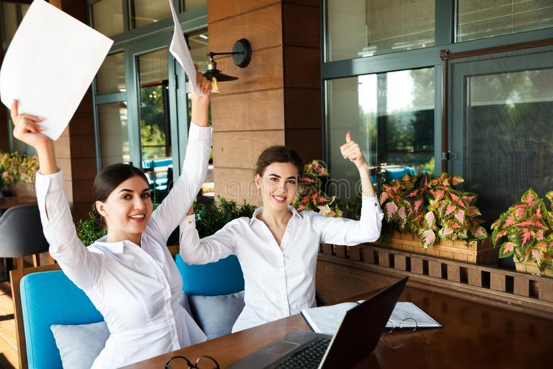 Happy smiling young businesswomen working on laptop in street cafe outdoor royalty free stock photo