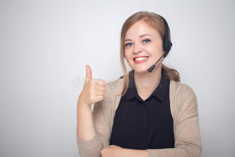 Happy smiling young caucasian woman with headset phone in a call center, thumbs up stock photo