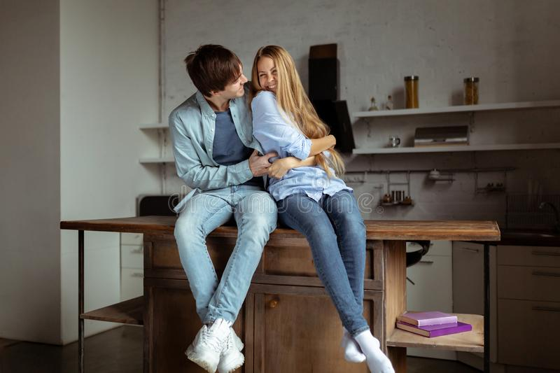Happy smiling young couple in blue denim cloth sitting in the kitchen stock images