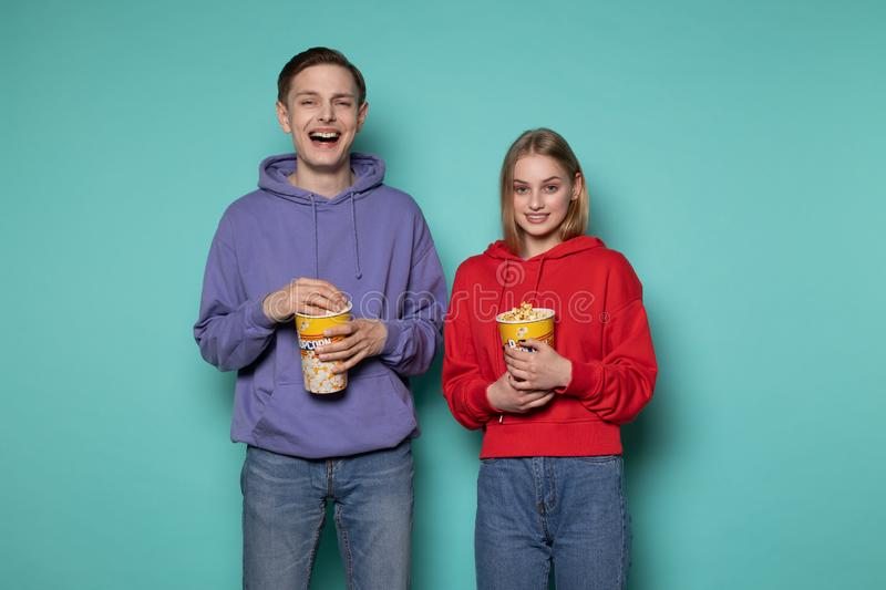 Happy smiling young couple in casual clothes standing against blue wall with popcorn in hands stock photos