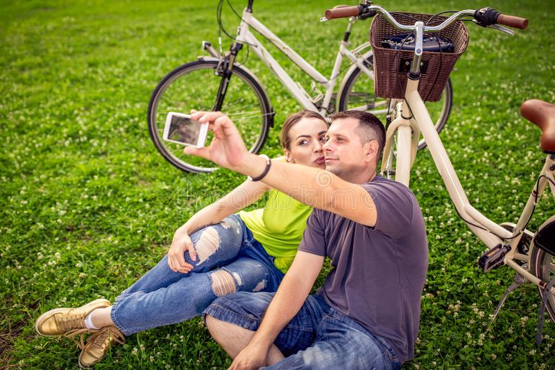 Smiling young couple taking selfie stock image
