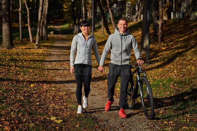 Happy young couple going for a bike ride on an autumn day in the park. royalty free stock image