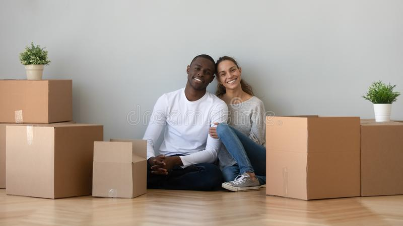 Happy smiling young mixed race family couple sitting on floor. royalty free stock image