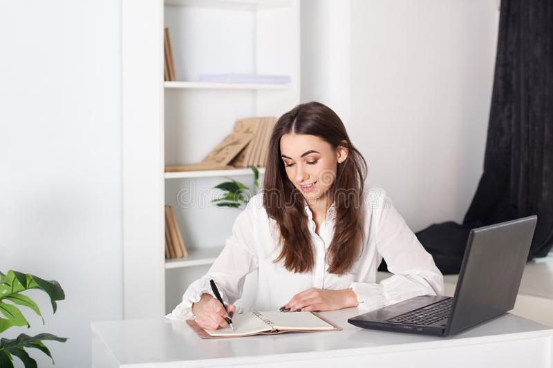 Happy smiling young girl working in the office. The girl writes in a notebook. Close-up portrait of an office worker. Positive you royalty free stock images
