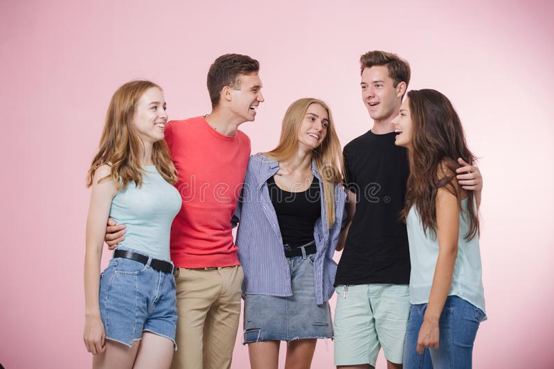 Happy smiling young group of friends standing together talking and laughing. Best friends royalty free stock image