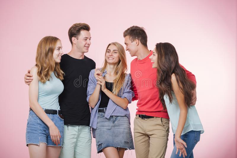 Happy smiling young group of friends standing together talking and laughing. Best friends stock photography