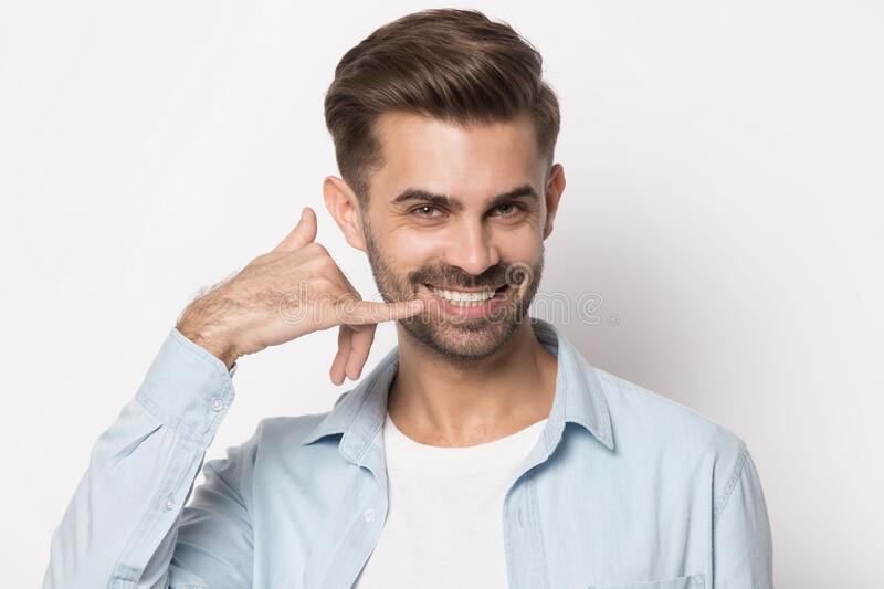 Happy smiling young guy showing call me back gesture. stock images