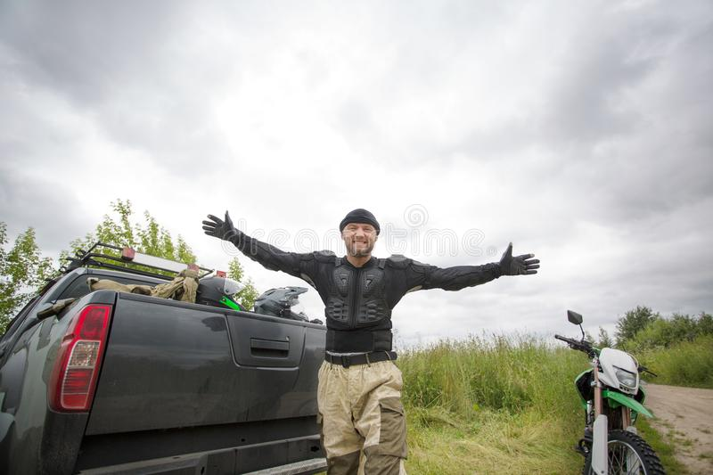 Happy smiling young man with arms wide open outdoors wearing mot. Orcycle gear and looking at the camera, truck with helmets and dirt bike on the scenic stock images