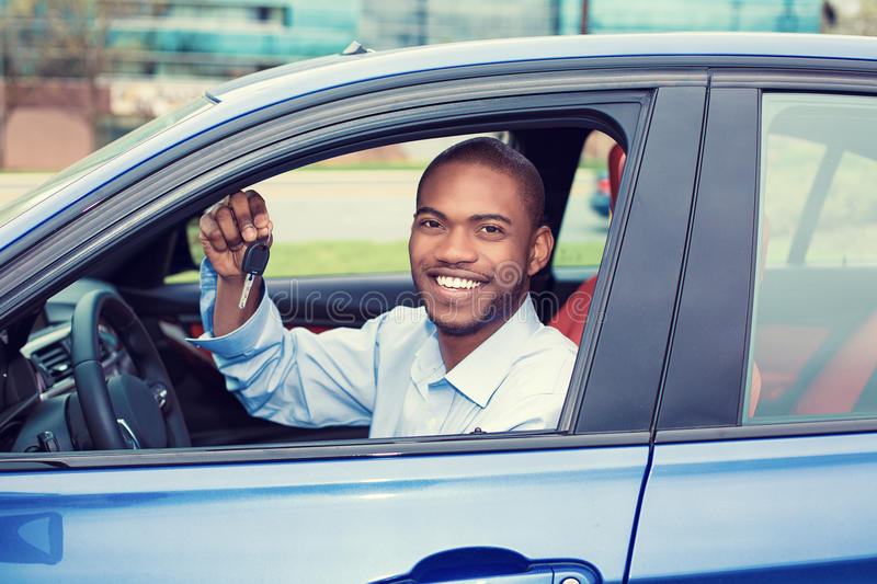 Happy, smiling, young man, buyer sitting in his new blue car showing keys. Closeup portrait happy, smiling, young man, buyer sitting in his new blue car showing royalty free stock image