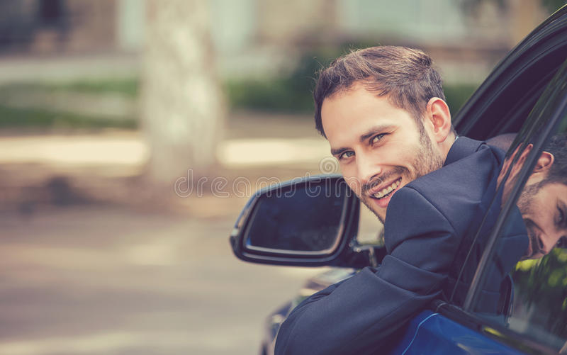 Happy smiling young man buyer sitting in his new car. Closeup portrait happy smiling young man buyer sitting in his new car excited ready for trip isolated royalty free stock image