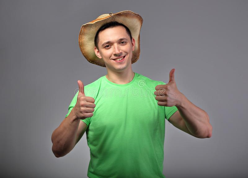 Happy smiling young man in hat showing thumb up by two hands in green summer shirt on grey background stock images