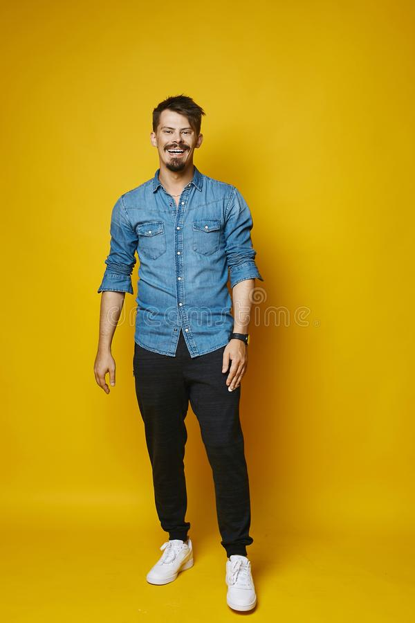 Happy and smiling young man, stylish hipster with beard and mustache in fashionable jeans shirt at yellow background royalty free stock photography