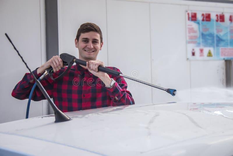 Happy smiling young man washing his car at pressure car wash stock image