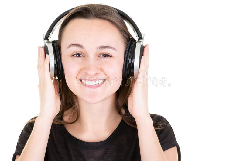 Happy smiling young pretty woman with headphones enjoying music hands on DJ headset stock photography