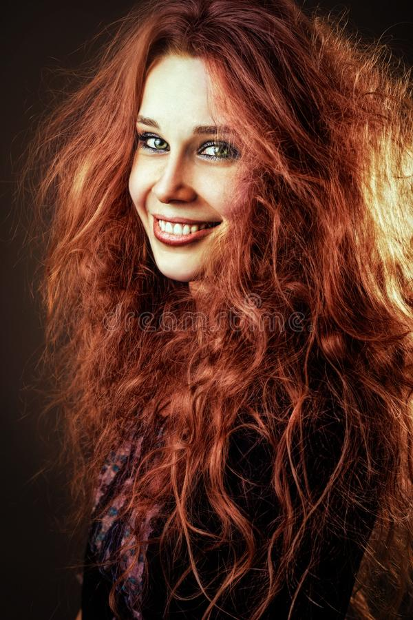 Happy smiling young redhead woman with long curly hair royalty free stock images