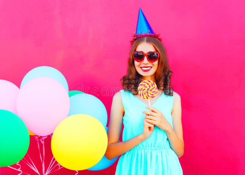 Happy smiling young woman in a birthday cap with an air colorful balloons and lollipop on stick over pink background. Happy smiling young woman in a birthday cap stock photography
