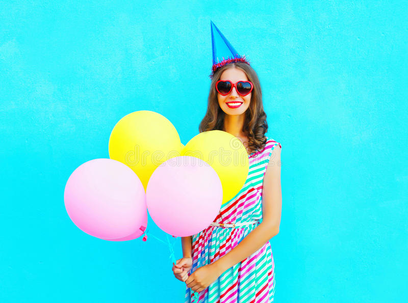 Happy smiling young woman in a birthday cap with an air colorful balloons over a blue. Background stock photography