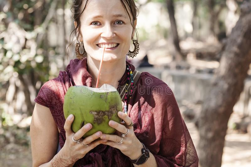 Happy smiling young woman with coconut royalty free stock images