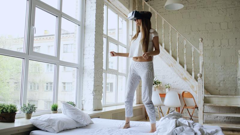 Happy smiling young woman dancing while getting experience using 360 VR headset glasses of virtual reality on bed at royalty free stock photo