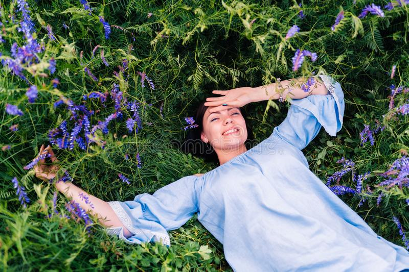 Happy smiling young woman falling down on grass with violet flowers. Beautiful girl lying in field. Enjoying nature. stock image