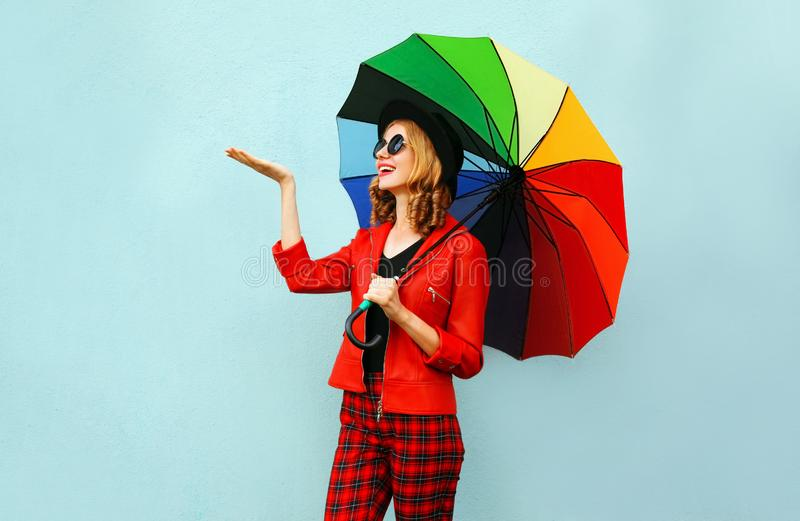 Happy smiling young woman holding colorful umbrella, checking with outstretched hand rain, wearing red jacket, black hat on blue royalty free stock photos