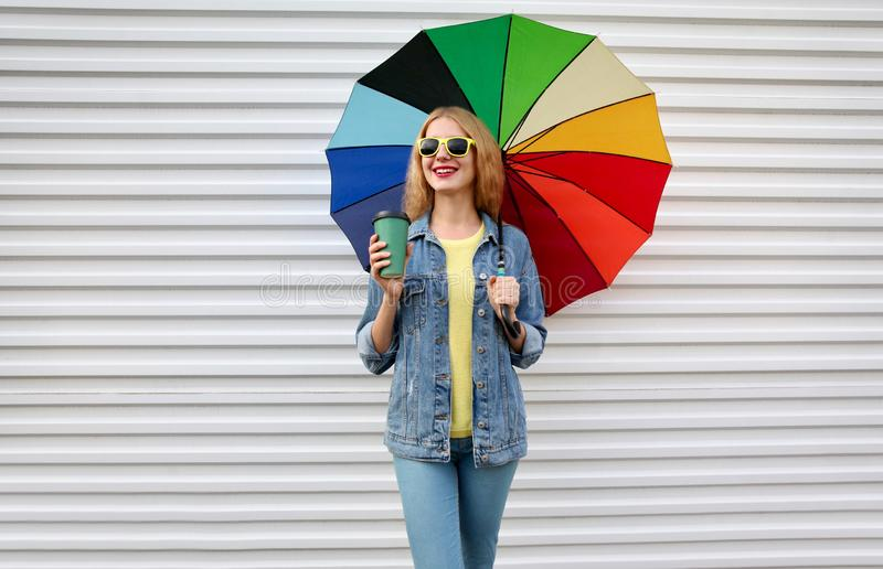 Happy smiling young woman holding colorful umbrella, coffee cup on white wall royalty free stock images