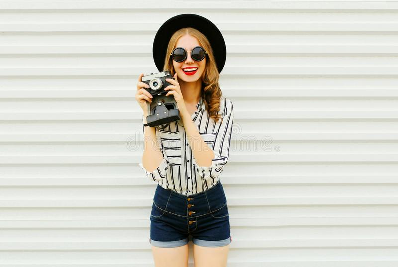 Happy smiling young woman holding vintage film camera in black round hat, shorts, white striped shirt on white wall. Background royalty free stock photo