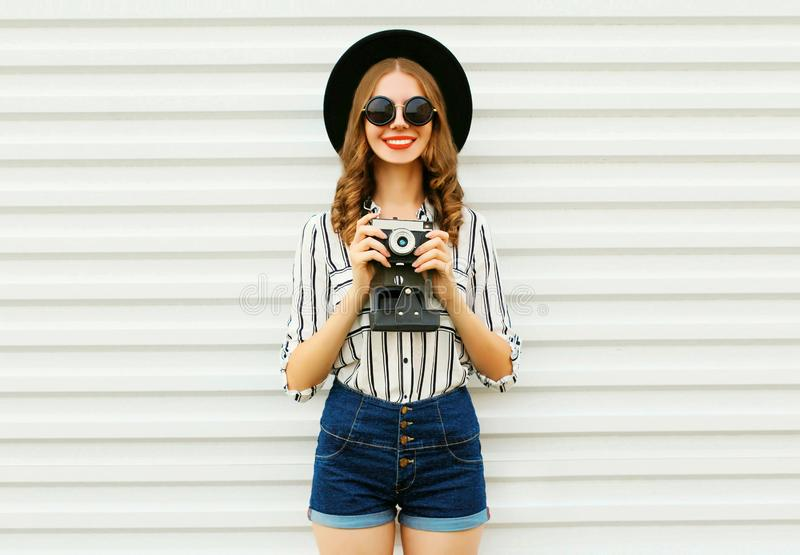 Happy smiling young woman holding vintage film camera in black round hat, shorts, white striped shirt on white wall royalty free stock images