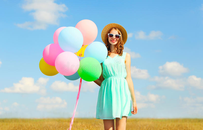 Happy smiling young woman holds an air colorful balloons enjoying a summer day on a meadow blue sky stock images