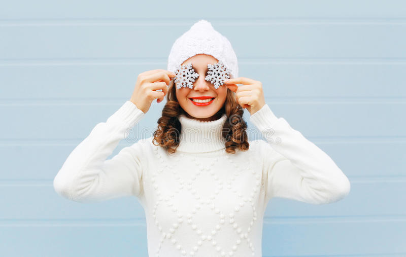 Happy smiling young woman in knitted hat and sweater with snowflakes on a face having fun over blue background. Happy smiling young woman in knitted hat and stock images