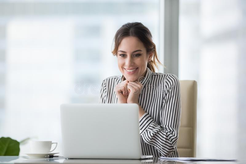 Happy smiling young woman looking at laptop screen. Excited businesswoman received good business offer, business email. Receiving good news concept, got stock photography