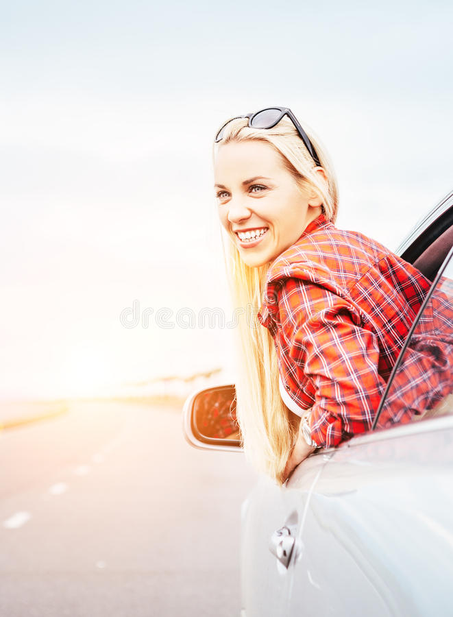 Happy smiling young woman looks out from car window stock photo