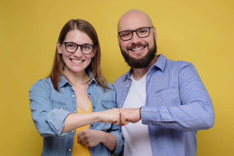 Happy smiling young woman and man friends couple give fist bump looking at camera. Friendship partnership respect or being team together stock photo