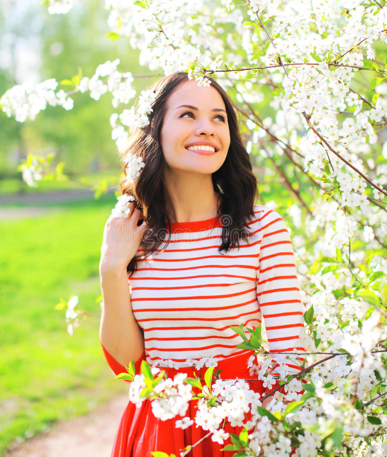 Happy smiling young woman over spring flowers royalty free stock image