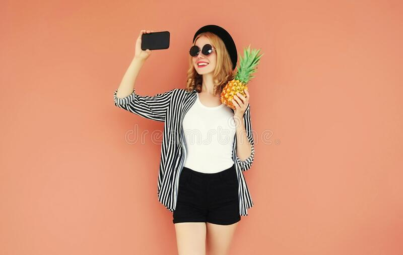 Happy smiling young woman with pineapple taking selfie picture by smartphone on background stock photos