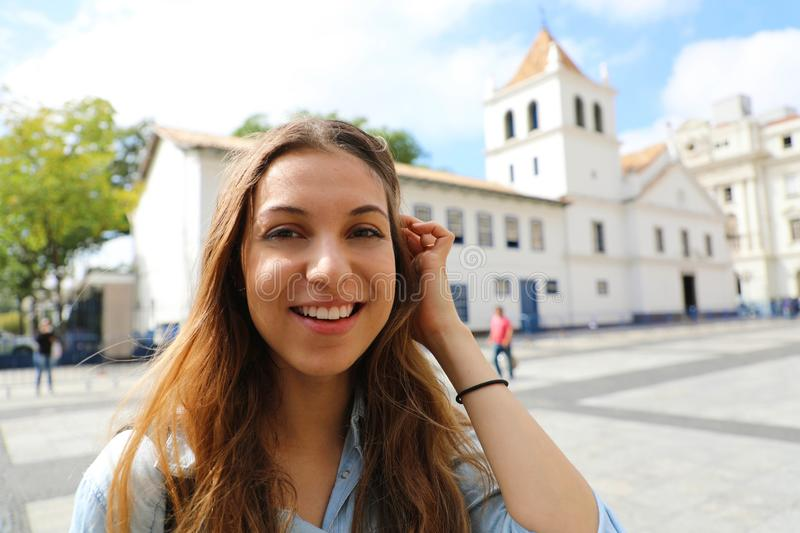 Happy smiling young woman in Sao Paulo city center with Patio do Colegio landmark on the background, Sao Paulo, Brazil royalty free stock photography