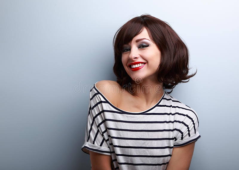 Happy smiling young woman with short hair on blue stock photo