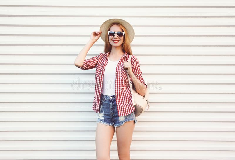 Happy smiling young woman in summer round straw hat, checkered shirt, shorts posing on white wall. Background stock photography