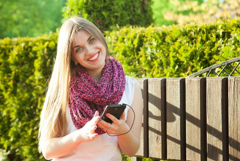 Happy smiling young woman using her phone outdoors royalty free stock images