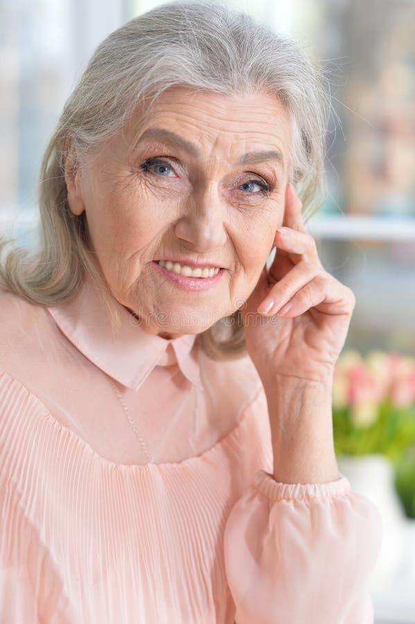 Happy smilling senior woman posing at home stock image